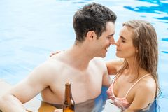 Beautiful young couple in love together in swimming pool ,rubbin. G nose as a sign of love and about to kiss Royalty Free Stock Photos