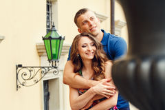 Beautiful young couple in love walking on urban background. Holding hands Royalty Free Stock Images