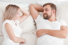 Sensual young couple together in bed. Happy couple in bedroom  on a white background. Beautiful young couple lying on the bed smiling and looking at each other Stock Images