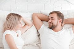 Sensual young couple together in bed. Happy couple in bedroom  on a white background. Beautiful young couple lying on the bed smiling and looking at each other Royalty Free Stock Photos