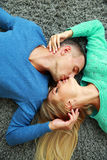 Beautiful young couple lying on the carpet Royalty Free Stock Photography