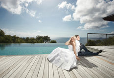 Beautiful young couple lying close to pool before wedding under Stock Images