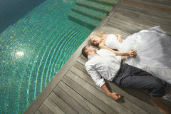 Beautiful young couple lying near pool with mind waves. Beautiful young couple lying close to pool before wedding. Warm summer day, wedding preparations at Royalty Free Stock Photo
