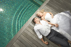 Beautiful young couple lying near pool with mind waves. Beautiful young couple lying close to pool before wedding. Warm summer day, wedding preparations at Royalty Free Stock Photography
