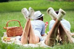 Happy young couple lying next to each other and eating watermelons, picnic in a park. View from behind royalty free stock photography
