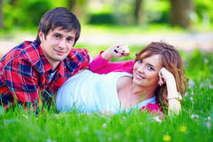 Beautiful young couple lying in spring grass Royalty Free Stock Photography