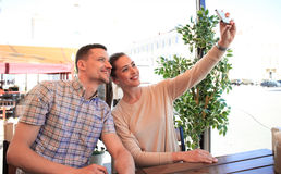 Beautiful young couple is making selfie using a smartphone and smiling while sitting in the cafe. Stock Image