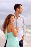 Beautiful young couple at the ocean. Portrait of beautiful young couple at the ocean, he is distracted by the sea, she is looking at the viewer smiling Royalty Free Stock Images