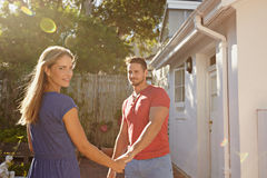 Beautiful young couple outside their house. Portrait of beautiful young women holding hand of her boyfriend and looking at camera. Young couple outdoors in their stock images