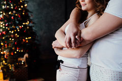 Beautiful young couple in pajamas on nicely decorated Christmas tree background. Royalty Free Stock Photos