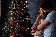 Beautiful young couple in pajamas on nicely decorated Christmas tree background. Royalty Free Stock Photo