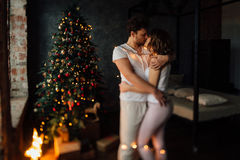 Beautiful young couple in pajamas on nicely decorated Christmas tree background. Royalty Free Stock Photography