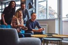 Beautiful young couple playing video games with friends. In the living room Royalty Free Stock Photography