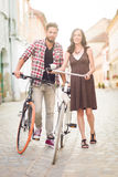 Beautiful young couple posing beside bicycle Royalty Free Stock Photos