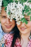 Beautiful young couple posing and smiling under white flowers in spring garden. Portraits of happy family embracing at blooming stock photo