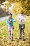 Beautiful young couple preparing their watches for run in the park. Autumn environment Royalty Free Stock Image