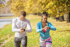 Beautiful young couple preparing their watches for run in the park. Autumn environment Stock Photo