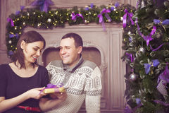 Beautiful young couple with present near christmas tree Royalty Free Stock Photos