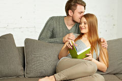 Beautiful young couple reading a book on the sofa Stock Image