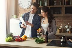 Beautiful young couple reading recipe on tablet. Beautiful young couple is using a digital tablet and reading the recipe on culinary website while cooking in Royalty Free Stock Photography