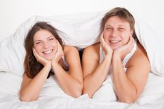 Beautiful young couple relaxing in bed at home Stock Images
