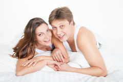 Beautiful young couple relaxing in bed at home Stock Photo