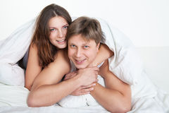 Beautiful young couple relaxing in bed at home Royalty Free Stock Images