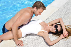An beautiful young couple relaxing by the poolside Stock Photos