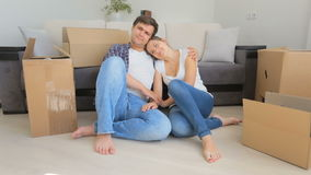 Beautiful young couple resting on floor after unpacking boxes at their new apartment stock video