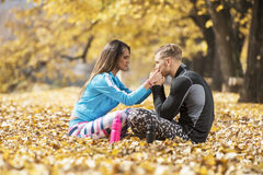 Beautiful young couple resting and kissing after successful training in the park Stock Photo