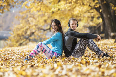 Beautiful young couple resting and listening music after successful training in the park. Autumn environment Stock Photos