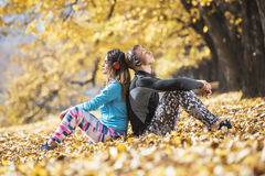 Beautiful young couple resting and listening music after successful training in the park. Autumn environment Stock Images