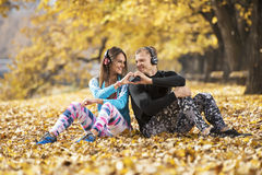 Beautiful young couple resting and listening music after successful training in the park. Hand shape heart. Autumn environment Royalty Free Stock Photography