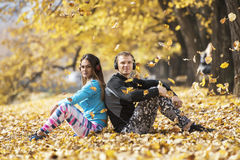 Beautiful young couple resting and listening music after successful training in the park. Hand shape heart. Beautiful young couple resting and listening music Stock Photo