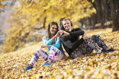 Beautiful young couple resting and listening music after successful training in the park. Hand shape heart. Autumn environment Royalty Free Stock Image
