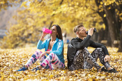 Beautiful young couple resting and rehydration after successful training in the park Royalty Free Stock Images