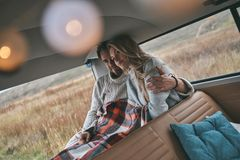 Best way to escape from the city. Beautiful young couple resting and smiling while sitting in retro style mini van Royalty Free Stock Photography
