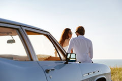 Beautiful young couple resting together outdoors while leaning on a car Stock Image