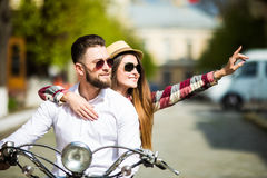 Beautiful young couple riding scooter together while happy woman pointing away and smiling royalty free stock images