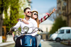Beautiful young couple riding scooter together while happy woman pointing away and smiling. Just look at that. Beautiful young couple riding scooter together Stock Image