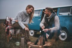 Perfect place to stay. Beautiful young couple roasting marshmallows over a campfire while enjoying their road travel stock photography