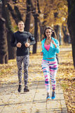 Beautiful young couple running together in the park Royalty Free Stock Images