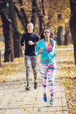Beautiful young couple running together in the park Stock Photography