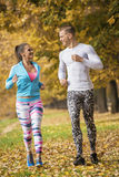 Beautiful young couple running together in the park. Royalty Free Stock Photos