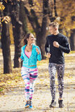 Beautiful young couple running together in the park. Stock Photo