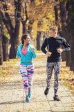 Beautiful young couple running together in the park. Royalty Free Stock Photo