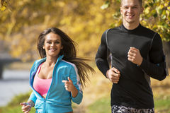 Beautiful young couple running together in the park. Stock Image