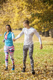 Beautiful young couple running together in the park. Man helps woman giving her hand Royalty Free Stock Photo
