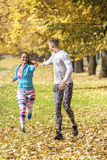 Beautiful young couple running together in the park. Man helps woman giving her hand Royalty Free Stock Images