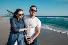 Beautiful young couple on the sandy beach of the sea royalty free stock image